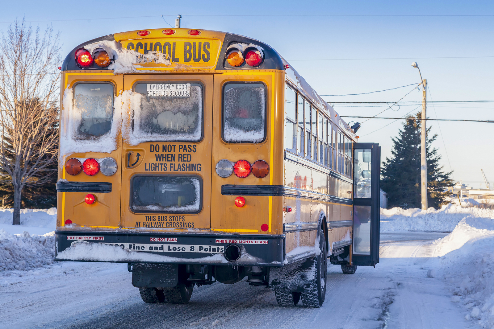 A typical yellow school bus stopped to pick up passengers on an