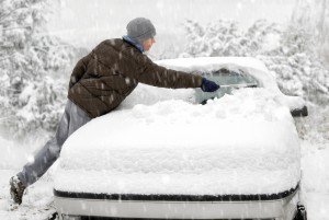 Man Brushes Snow Off His Car